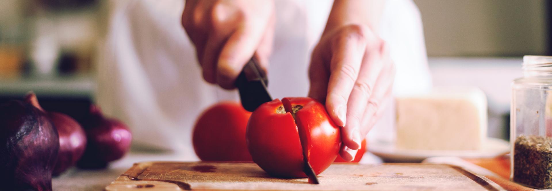 Mains de femme coupant une tomate