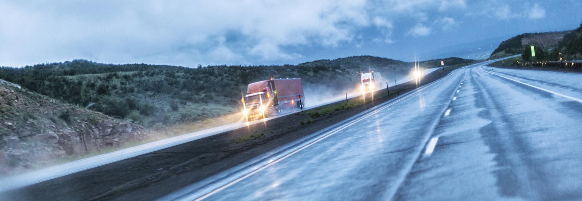 Camions sur autoroute de nuit au coucher du soleil et pluie