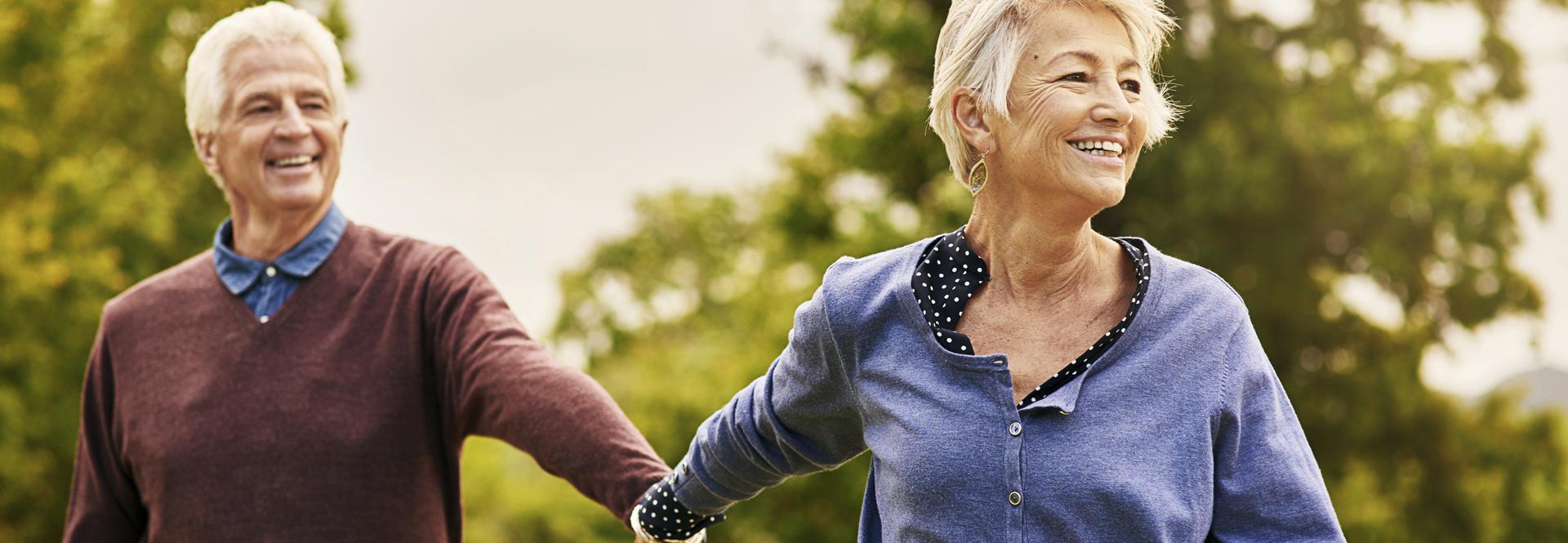 Couple de seniors heureux avance main dans la main