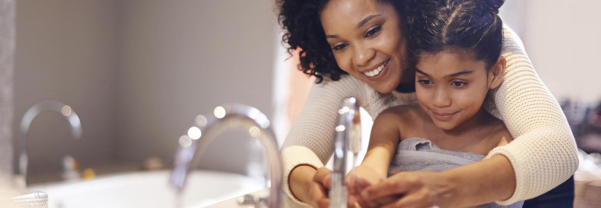 maman apprend à sa fille à se laver les mains